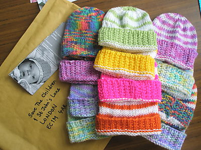 Twelve knitted baby hats lying on a jiffy bag addressed to Save The Children