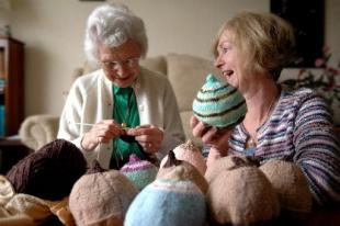 An elderly woman and a younger woman laughing over a selection of knitted 'breasts'