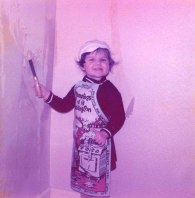 Small child wearing an apron, scraping wallpaper off a wall. The apron has a scene of Paddington Bear cooking messily, with the words 'Dumplings a la Paddington'
