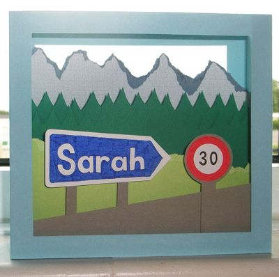 Front view of pop-up card showing Alpine landscape with road signs which read 'Sarah' and '30'