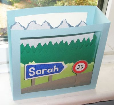 Aerial view of pop-up card showing Alpine landscape with road signs which read 'Sarah' and '30'
