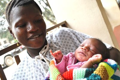 Happy new mum holding newborn baby wrapped in knitted blanket