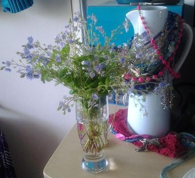 Bunch of small blue wildflowers standing in a drinking glass