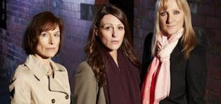 Three woman in a dark street, wearing winter clothes
