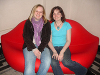 Two women sitting on a sofa shaped like a pair of lips