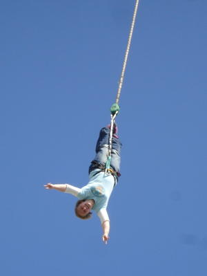 Woman hanging upside-down from a rope tied to her ankles, against a background of blue sky