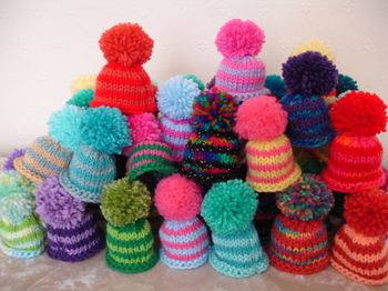 Pile of tiny knitted bobble hats in a variety of bright colours