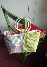 Handmade bag in fifties print and lime green corduroy, hanging on a green chair