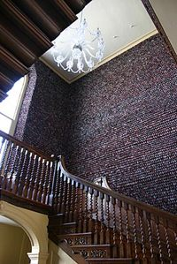 A stairwell covered in shells and red velvet